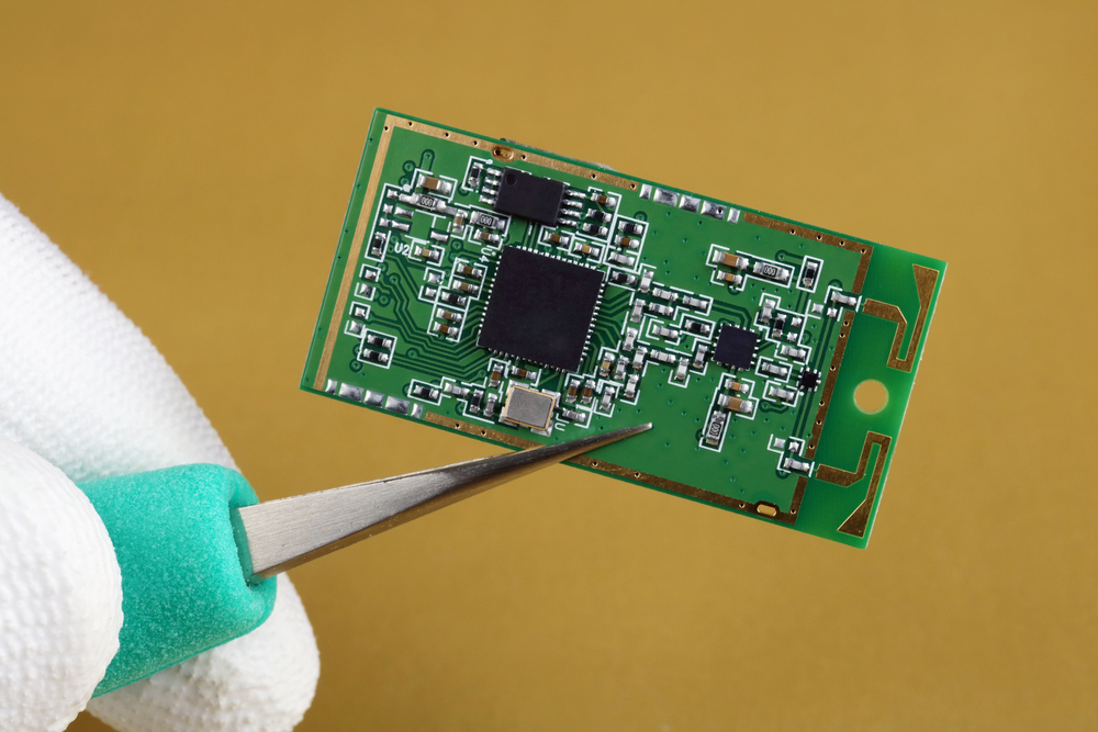 person holding a printed circuit board wireless bluetooth module with tweezers
